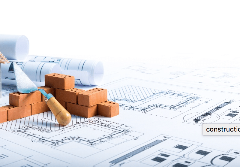 House under construction and a construction blueprint