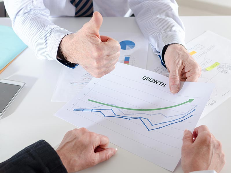 Person holding a piece of paper with a graph giving a thumbs up. Used as the header image for Viral Element's Sales Enablement page.